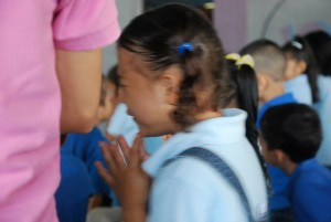 Honduran girl weeping in prayer